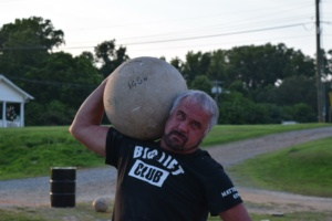 Man lifting concrete ball at a Big Lift Club at Matthew's Gym in Forest City, NC