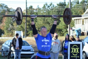 Man lifting weights during a Strongman and Strongwoman competition at Matthew's Gym in Forest City, NC