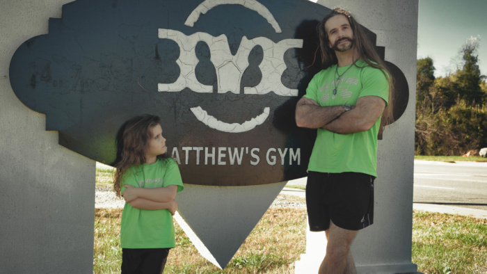 Matthew's Gym, Matthew Short and son standing at roadsign in Forest City, NC