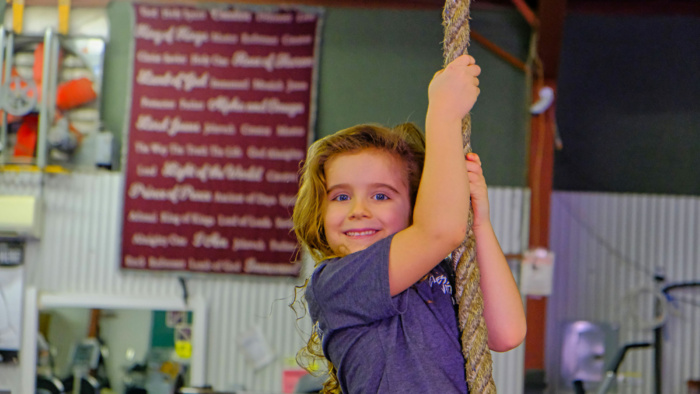 Matthew's son climbing a roap and smiling at the camera at Matthew's Gym